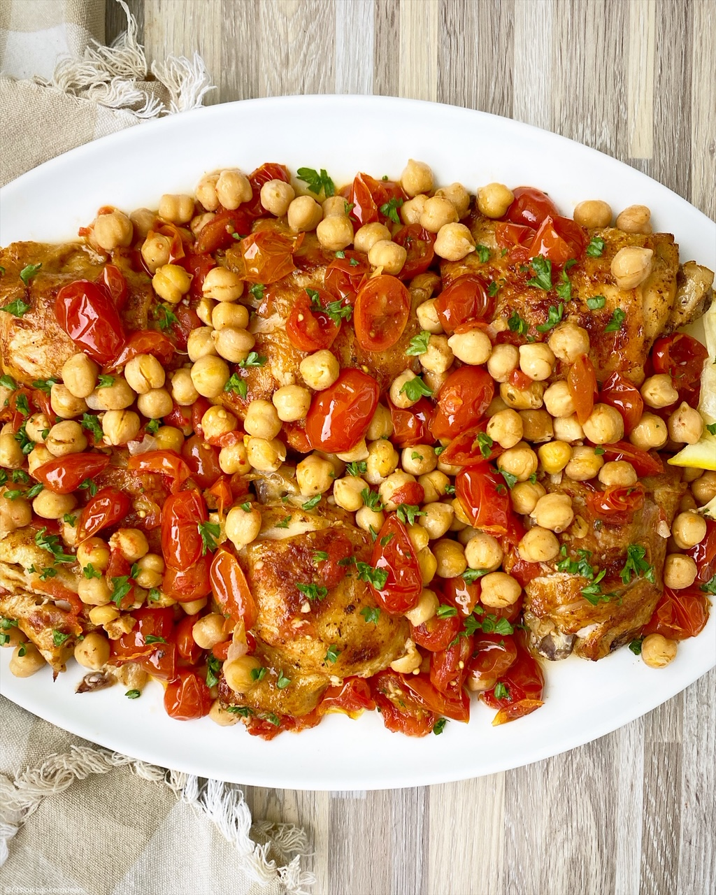 cooked chicken, chickepeas and tomatoes on a white serving platter