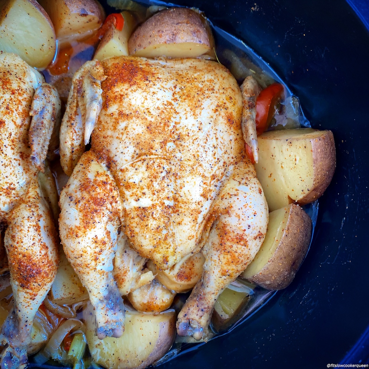 cooked creole seasoned Cornish hens in the slow cooker on top of potatoes, bell peppers, celery, and onions in the slow cooker with Creole seasoning on top