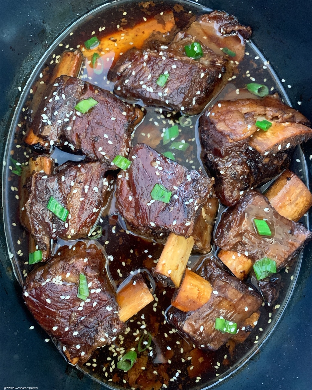 close up of korean style short ribs with sesame seeds and sliced green onions on top