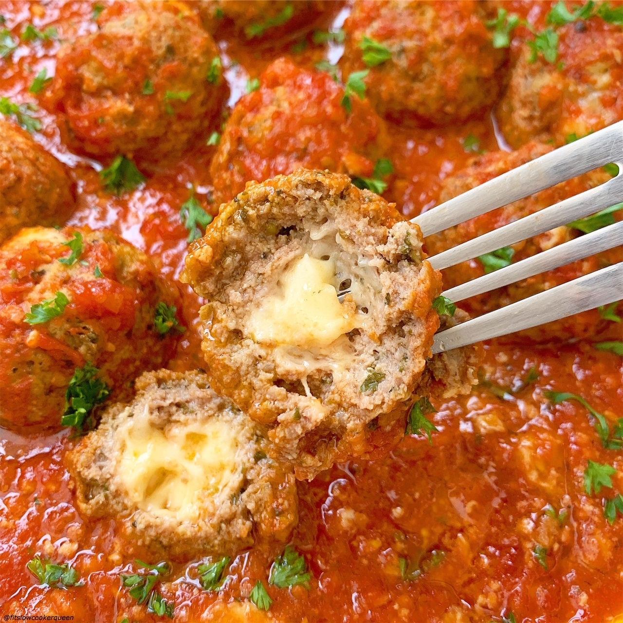 pic of an meatball with mozzarella cheese coming out of it from slow cooker instant pot mozzarella stuffed meatballs