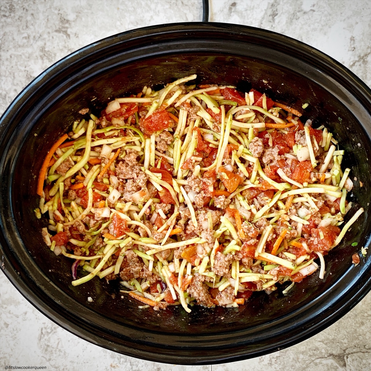 mixed raw slawghetti ingredients in the slow cooker