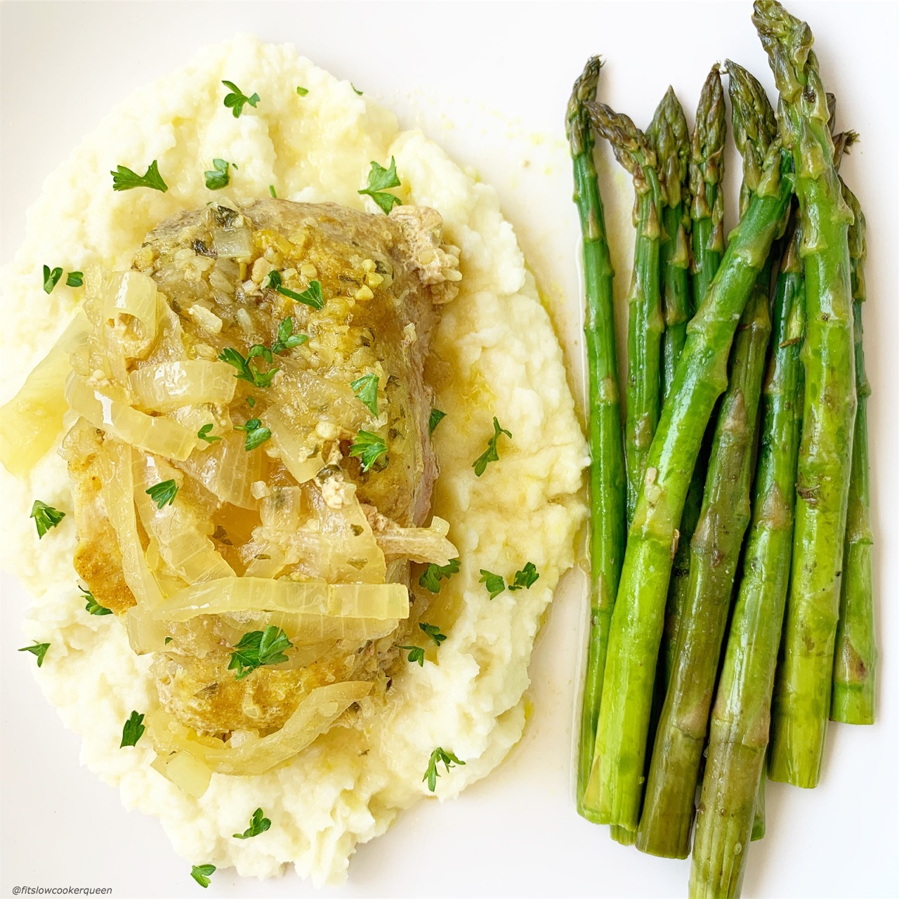 Front view of slow cooker french onion pork chops on top of mashed cauliflower and asparagus.
