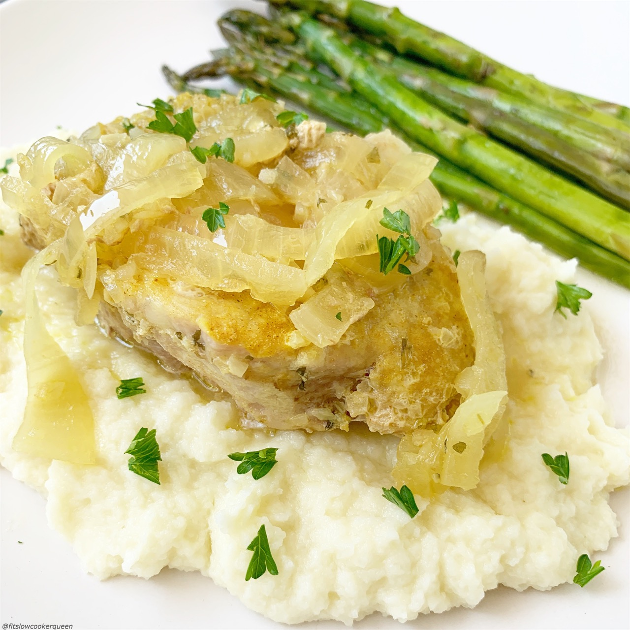 French onion pork chops on top of mashed cauliflower served with asparagus.