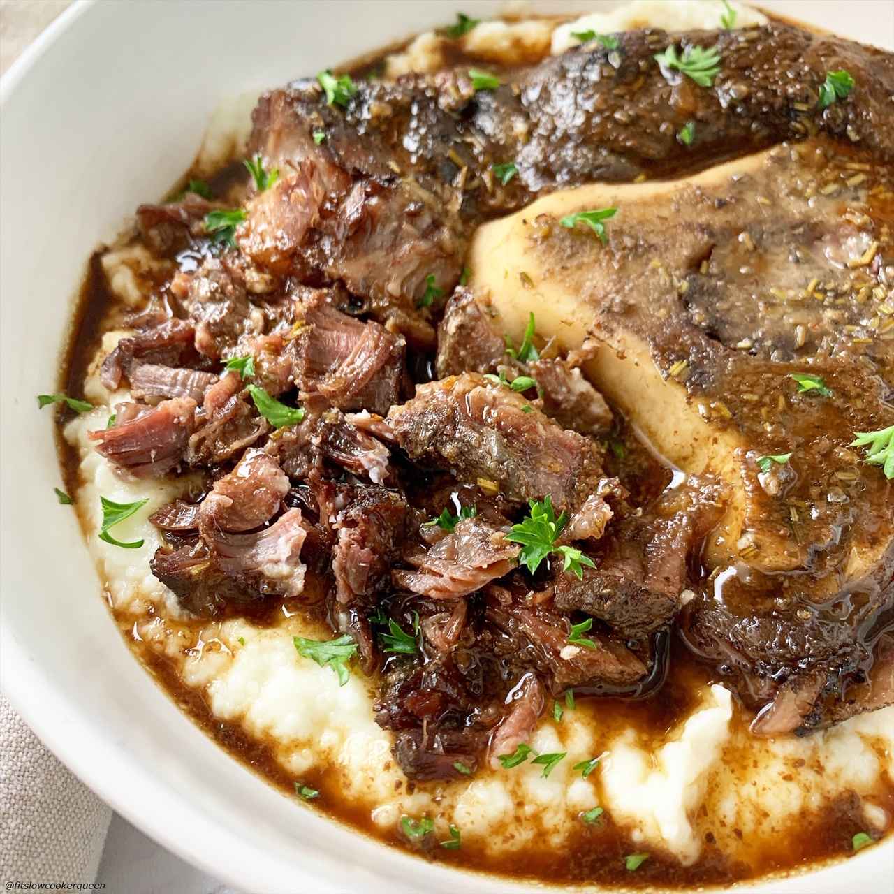close up of booked beef shanks with broth served over mashed potatoes