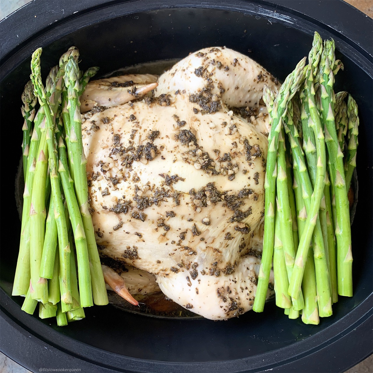 Cooked whole chicken in the slow cooker with asparagus added.