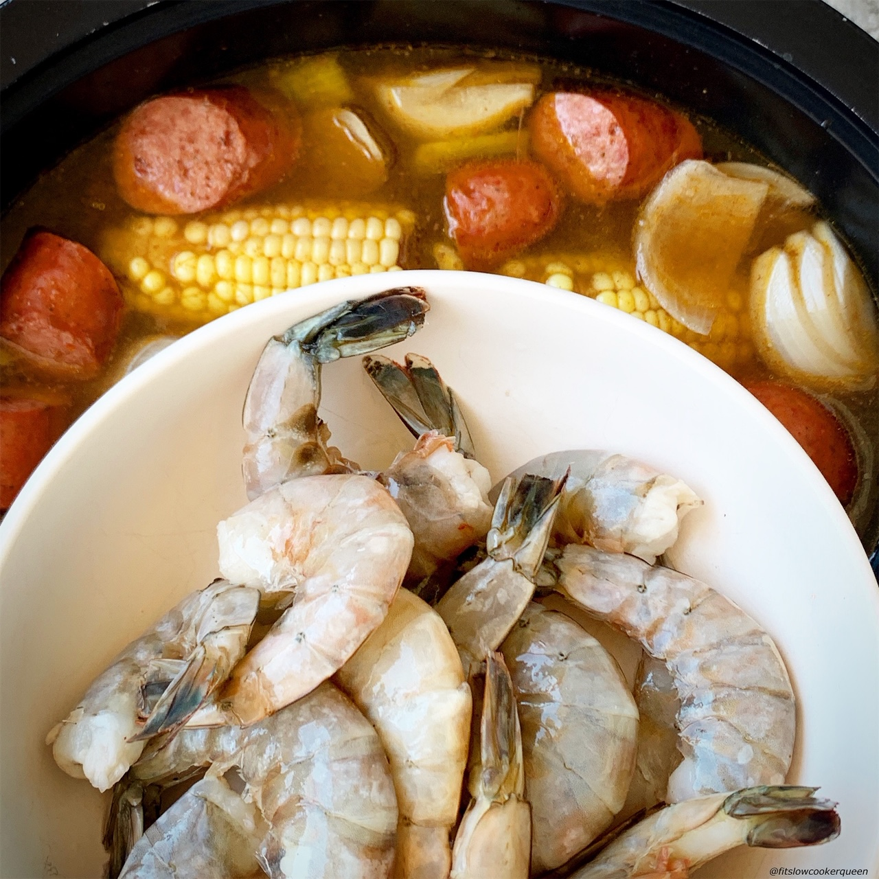 adding shrimp to the slow cooker for low country boil