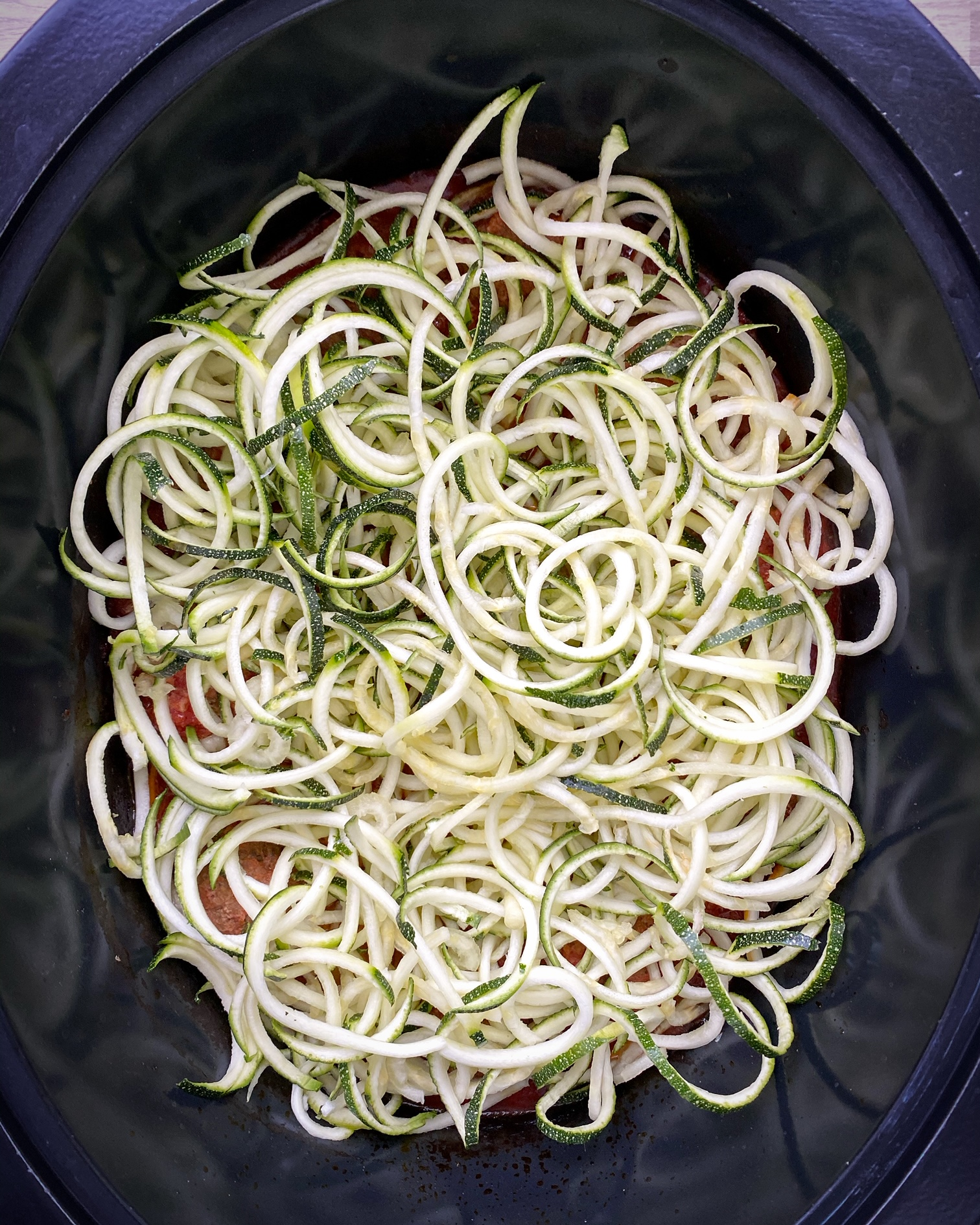 zoodles added on top of meatballs in the slow cooker