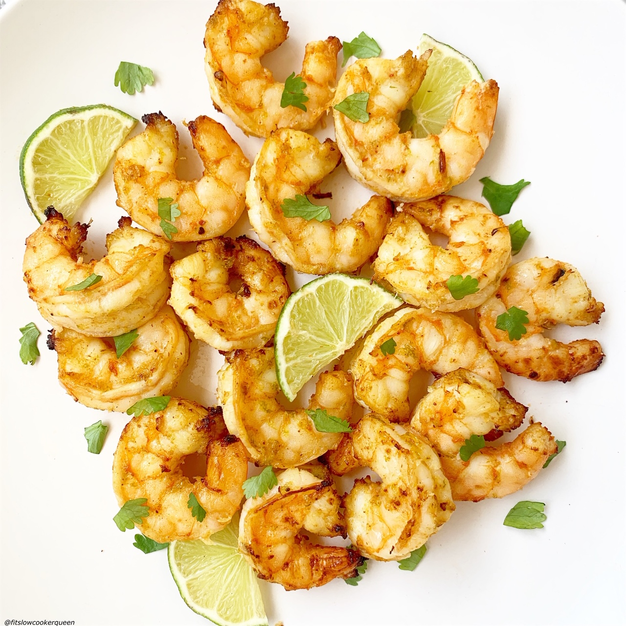 cooked air fryer shrimp on a plate with lime wedges and cilantro garnish