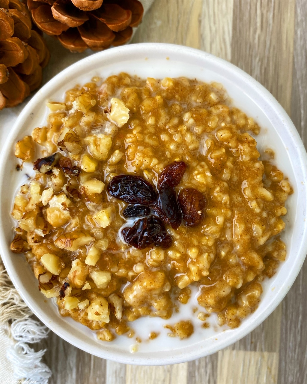 close up view of pumpkin oatmeal in a white bowl with raisins on top and almond milk