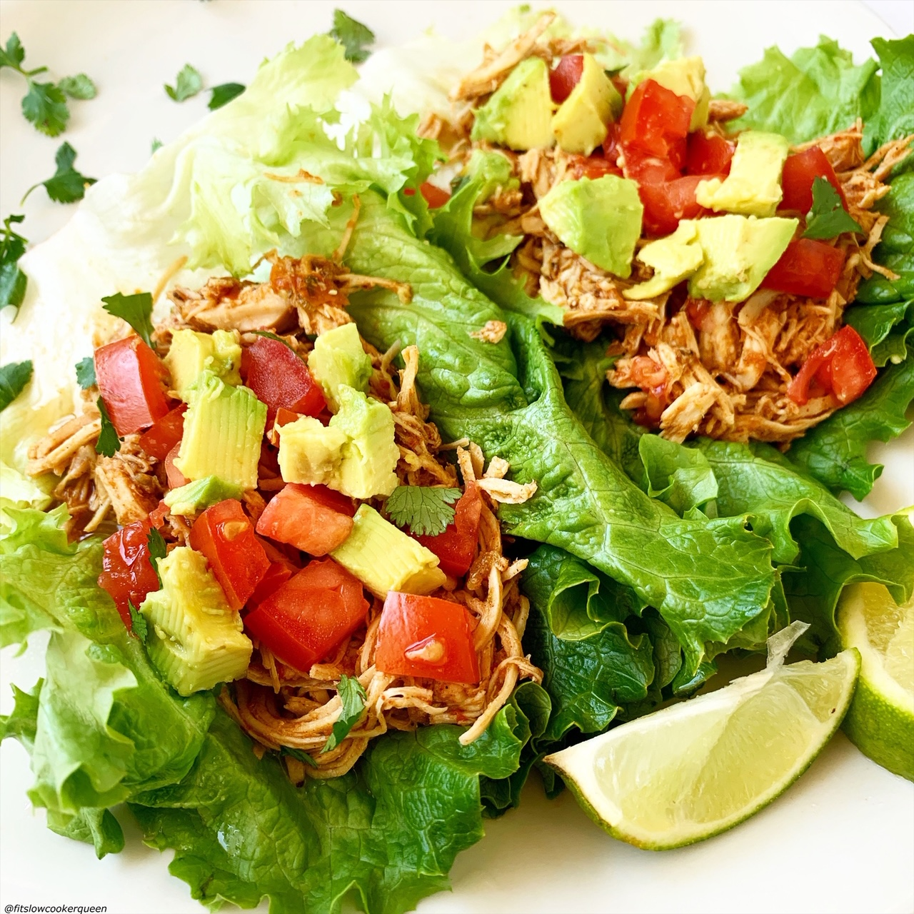 chicken tacos in a lettuce wrap topped with tomatoes, avocado, and lettuce