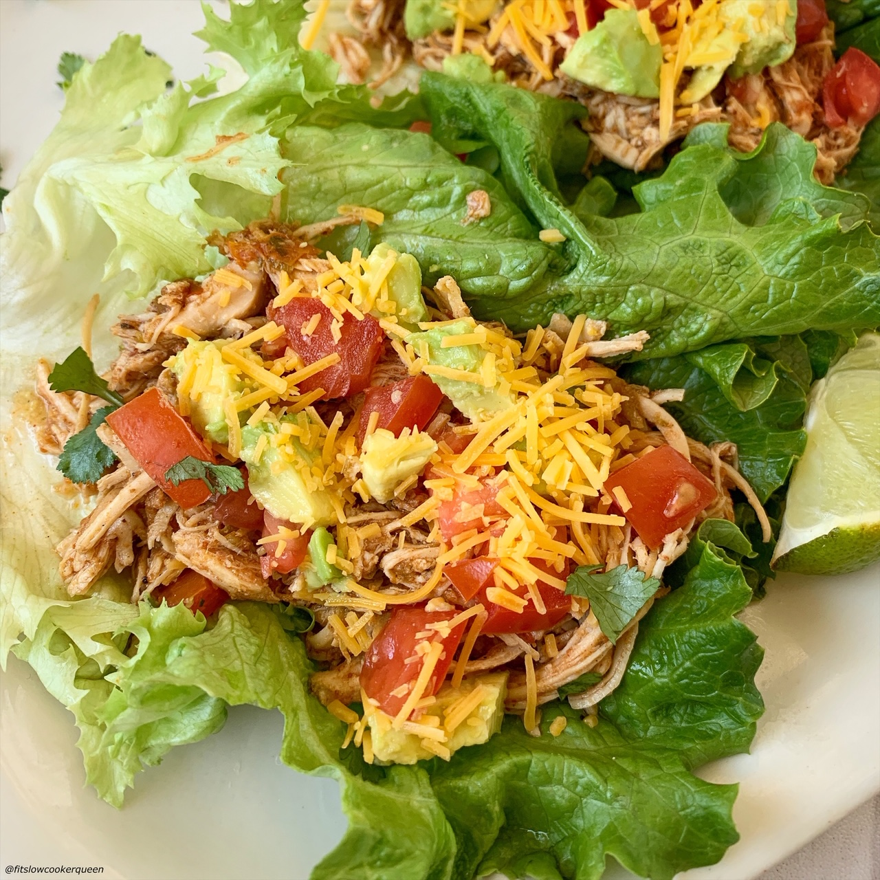 chicken tacos in a lettuce wrap topped with cheese, tomatoes, avocado, and lettuce