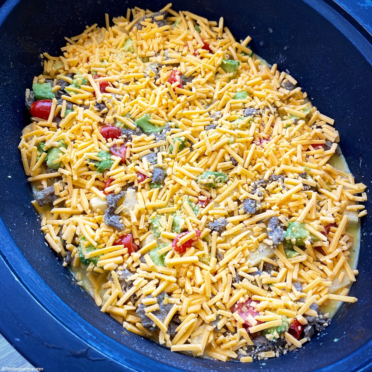 uncooked Slow Cooker California Burrito Breakfast Casserole in the slow cooker with eggs mixture poured on top