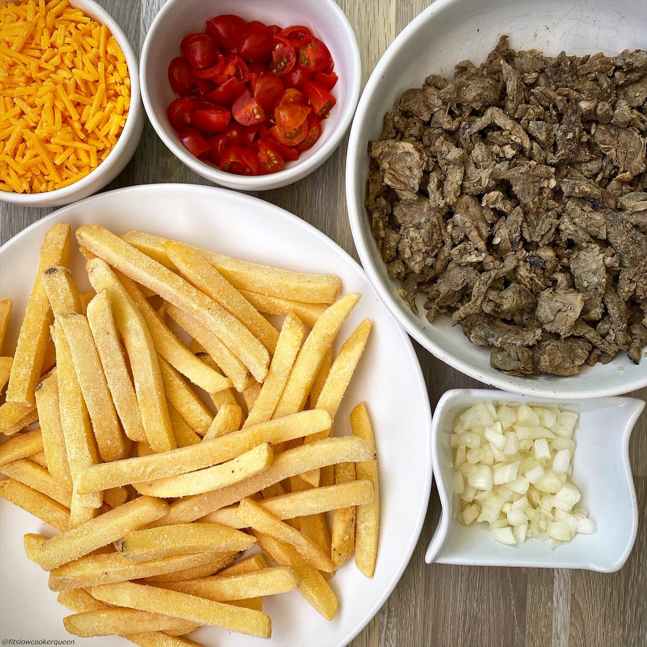 frozen french fries, cooked carne asada, shredded cheddar cheese, tomatoes, and onions in bowl