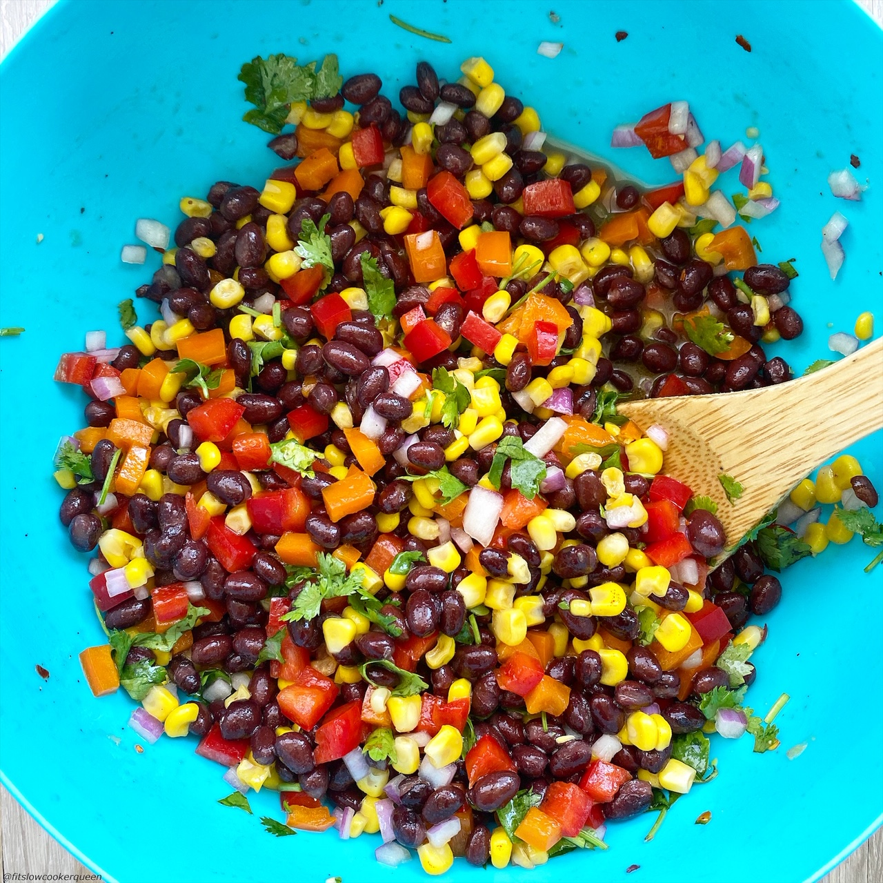 Mixed together in a large bowl: black beans, corn, diced orange bell pepper, diced red bell pepper, red onion, fresh cilantro