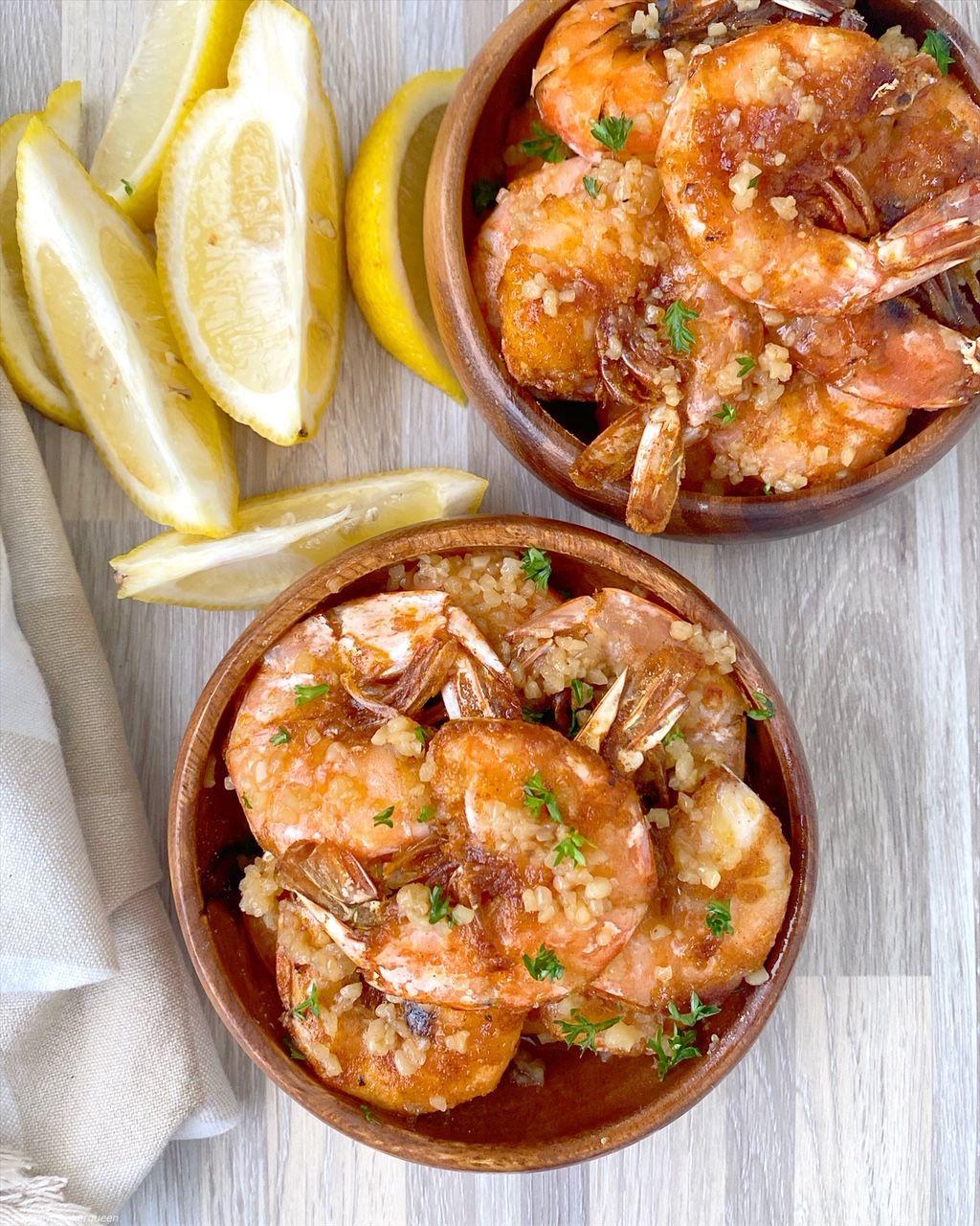 top view of cooked hawaiian shrimp with garlic on top in two separate bowls