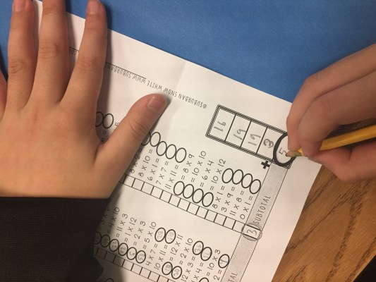 Kids correct their own multiplication facts tests.