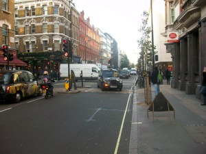 A taxi turns right into Gtreat Portland Street. The busy junction with Mortimer Street could have 40 double-decker buses an hour during the day and 20 an hour during the night pass through it. The bollards and traffic lights on the pedestrian island would have to be removed to allow the buses to be able to turn into this narrow street.