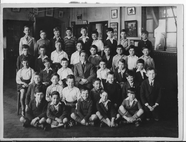 Group of boys sitting for school photograph.