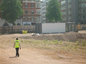 A security guard walks on patrol in the grounds of the former hospital