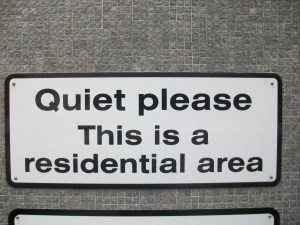 "A sign saying ""Quiet please. This is a residential area""."