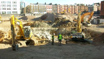 Construction workers standing in crater of Middlesex Hospital site.