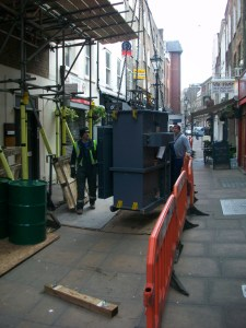 Electricity transformer being hoisted along street.