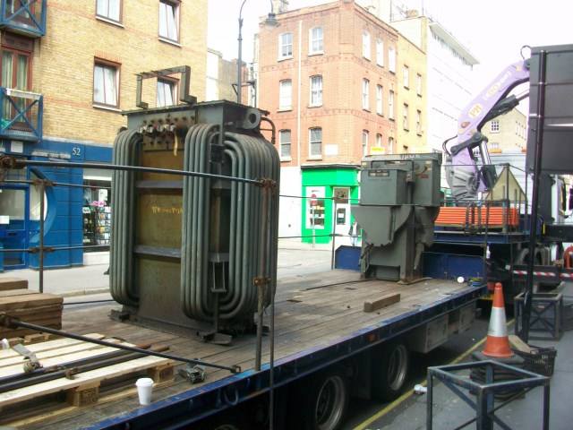 Old electricity transformer on the back of a flat bed lorry.