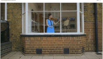 Woamn playing a violin in the window of a gallery.