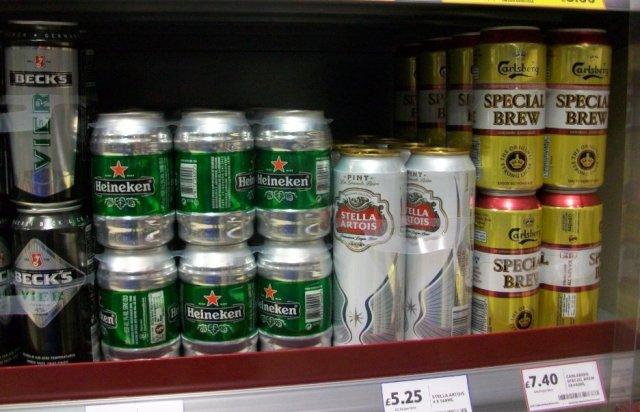 Cans of beer on supermarket shelf.
