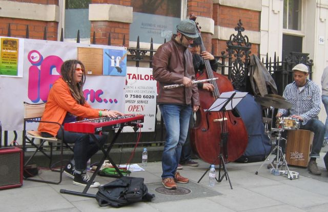 Four piece band playing live outside.