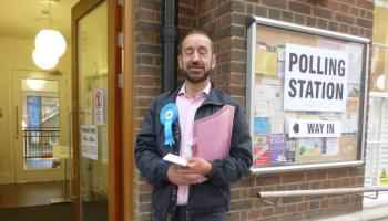 Councillor standing outside polling station.