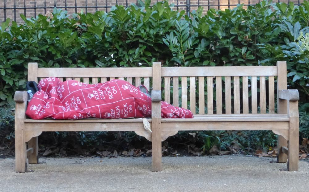 A man under a blanket on a park bench.