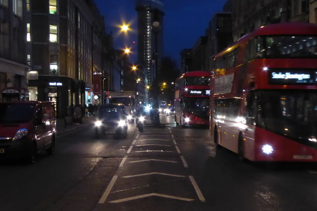 Motor traffic on Tottenham Court Road at night.