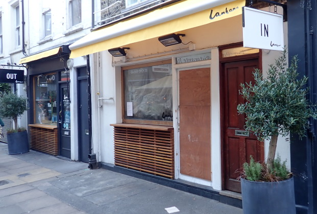 Front of restaurant boarded up.