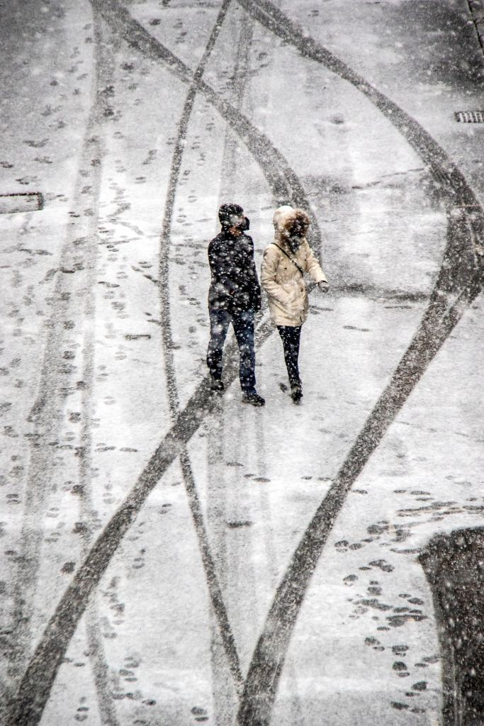 A couple walking in the snow along a street in Fitzrovia.