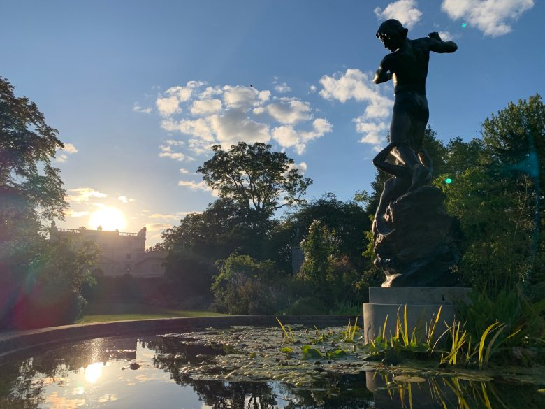 View of the garden at sunset with pond in the foreground.