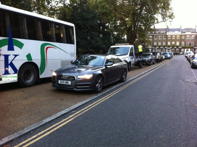 A coach, private hire vehciles, taxis and private cars parked on the pavement at Bedford Square.