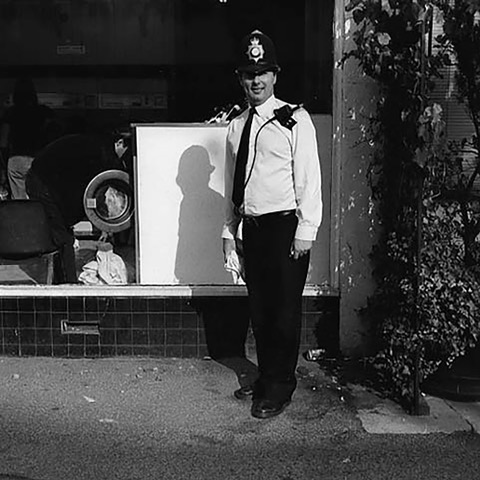 Policeman standing on street.