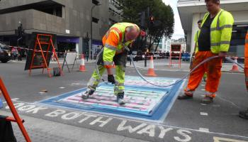 Two workers spray paint to create an artwork on Tottenhsm Court Road.
