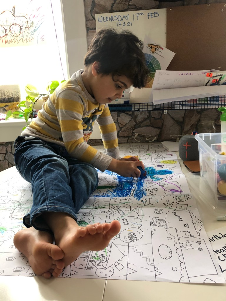 Boy coloring on a table.