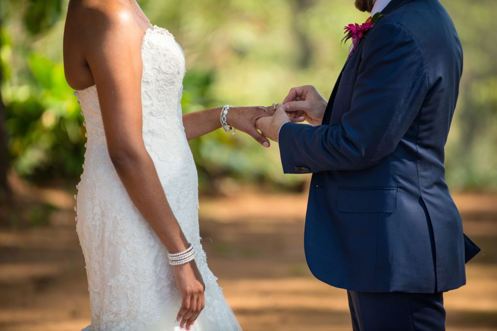 Wedding couple putting ring on finger of each other.