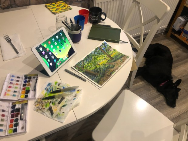 Table with watercolor painting and paints and dog lying on the floor.