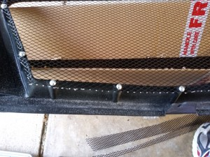 Adding screws to secure the mesh to the grille