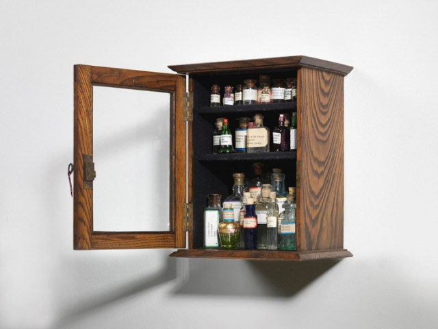 """Susan Hiller, """"Sa Testa: Homage to Joseph Beuys"""" Edwardian mahogany cabinet with lock and key, glass-fronted, containing 30 bottles of water collected from sacred springs, holy wells, etc. 6.3 x 9 x 11 inches (image courtesy TEFAF)"""