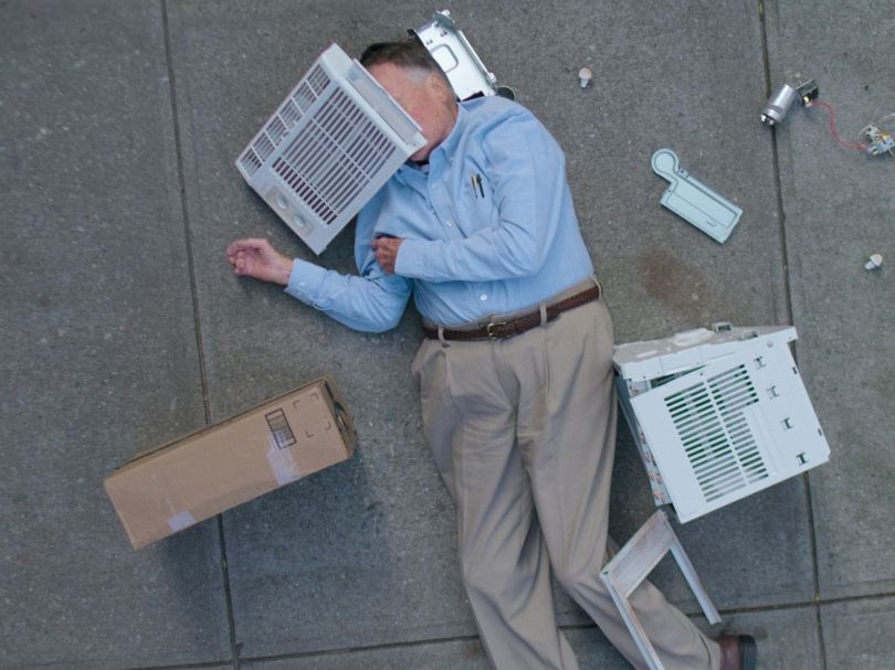 A man lays on a sidewalk, surrounded by the pieces of a broken air conditioner.