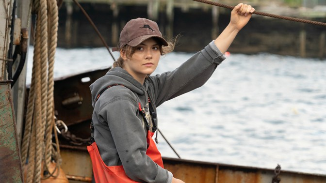 A teenager named Ruby sitting on a fishing vessel in the movie CODA