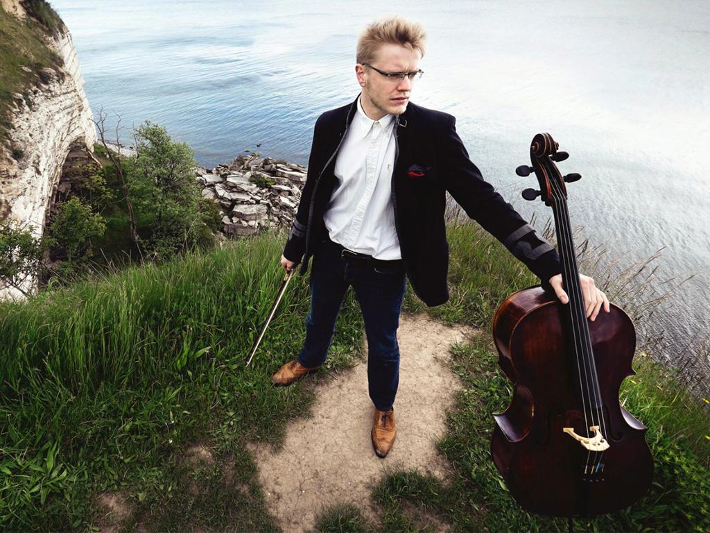 El violoncellista londinense Jacob Shaw sosteniendo su instrumento y detrás un paisaje escandinavo.
