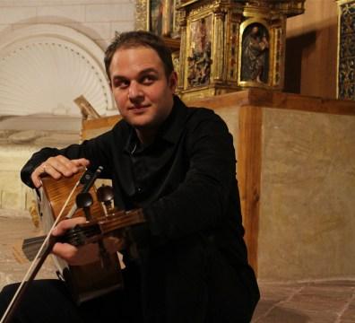 Retrato del violoncellista polaco Mikolaj Konopelski sosteniendo su violoncello