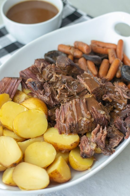 Slow cooker pot roast is the best weeknight dinner recipe for busy families. This easy pot roast recipe is made with a red wine sauce that makes the most amazing gravy after the pot roast cooks in the crockpot. #redwine #potroast #slowcooker #familyrecipe