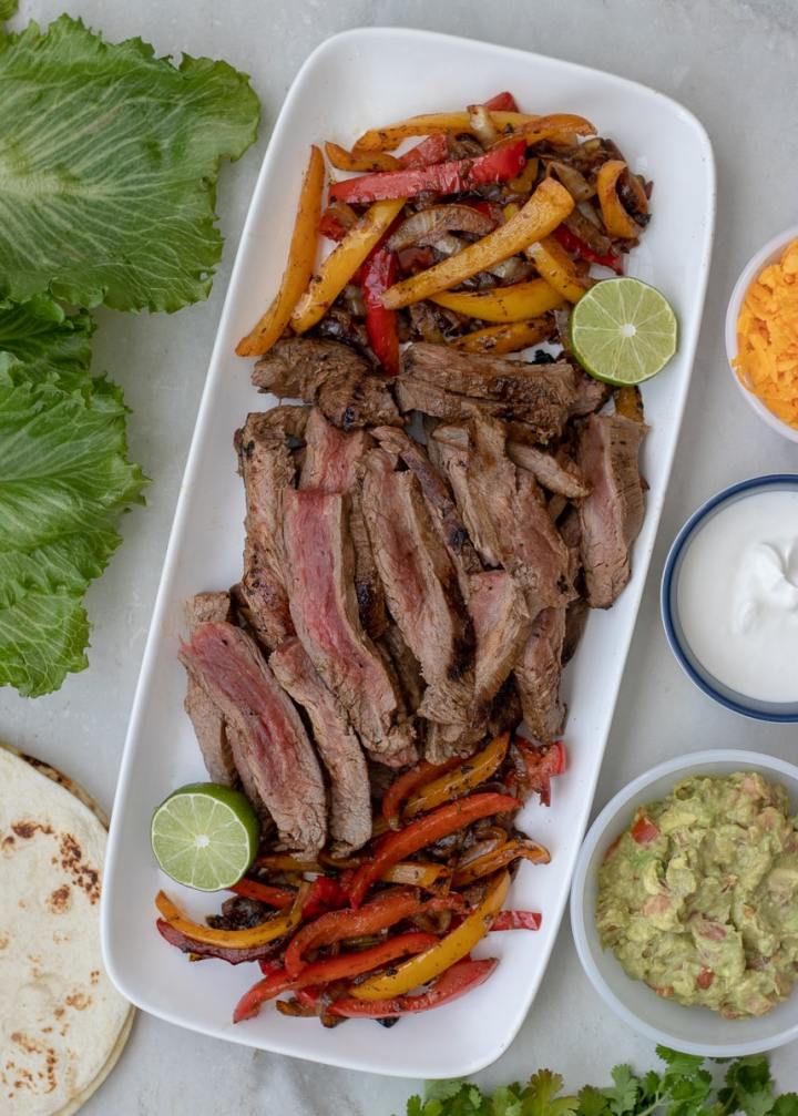 Pan seared flank steak fajitas marinated in a smokey citrus steak fajita marinade. Serve over greens or in lettuce boats to make them Whole30 and Paleo approved.